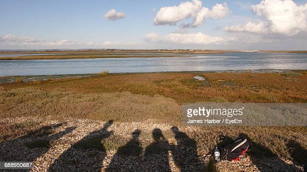Shadow Of People On Field By River Against Sky