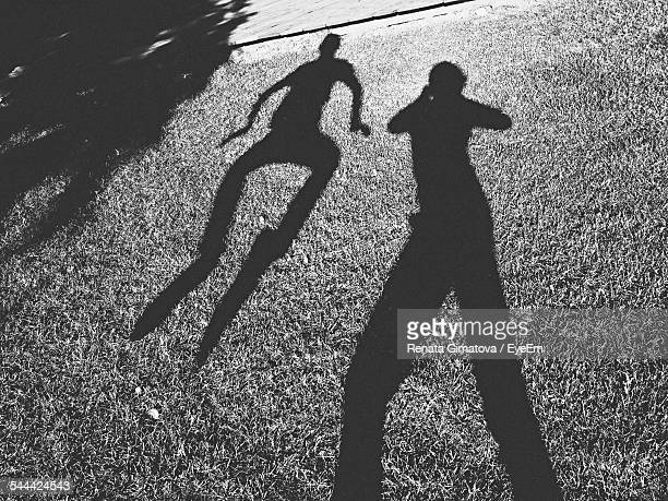 Shadow Of People On Grassy Field During Sunny Day