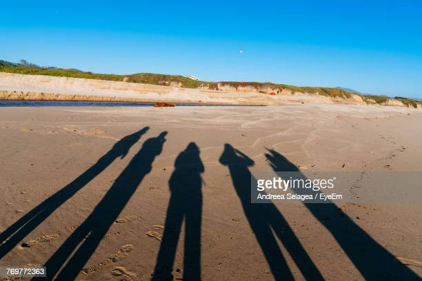 Shadow Of People On Sand At Beach Against Clear Sky