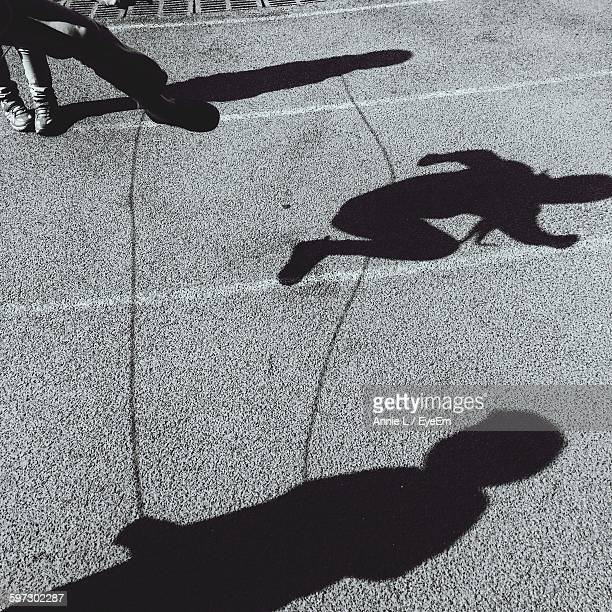 shadow of people playing jumping rope on street - 鄭州市 ストックフォトと画像