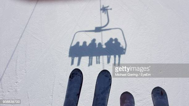 shadow of people sitting in ski lift on snow - ski lift stock pictures, royalty-free photos & images