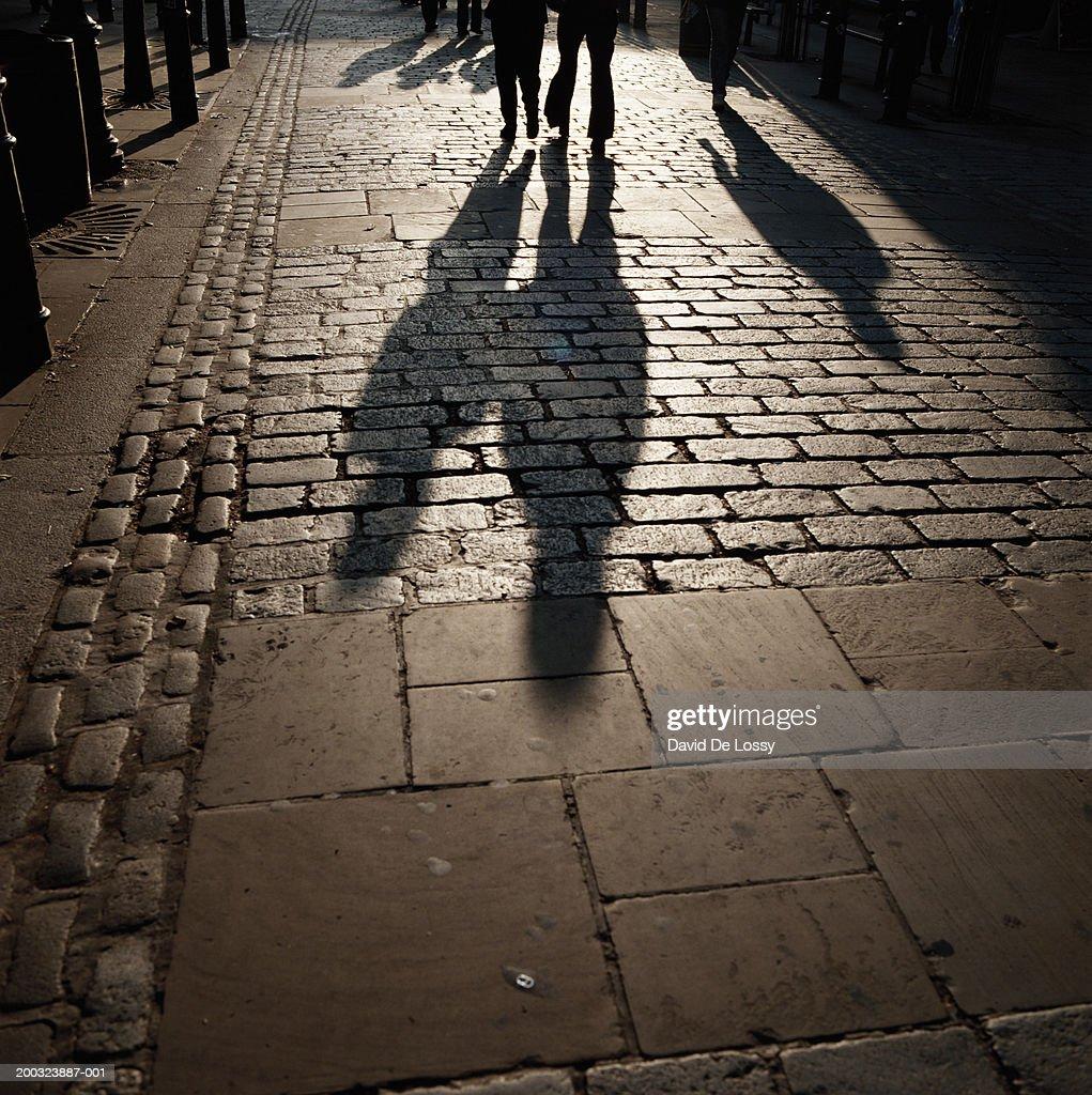 Shadow of people walking on footpath : Stock Photo