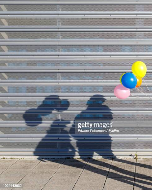 Shadow Of People With Balloon On Shutter