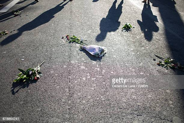 shadow of people with bouquets on street after terrorist attack - memorial event stock pictures, royalty-free photos & images