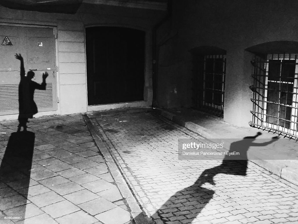 Shadow Of Person Falling On Building And Footpath Stock Photo