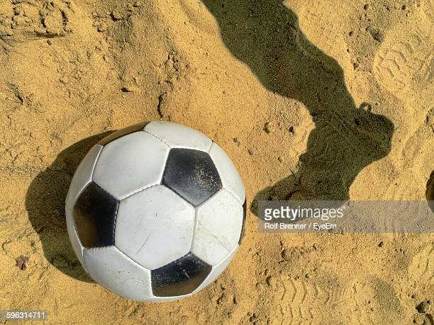 Shadow Of Person Leg With Soccer Ball On Sand