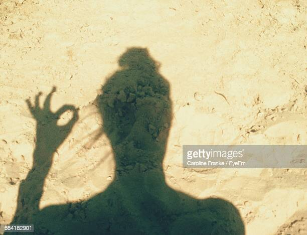 Shadow Of Person On Sand With Hand Sign