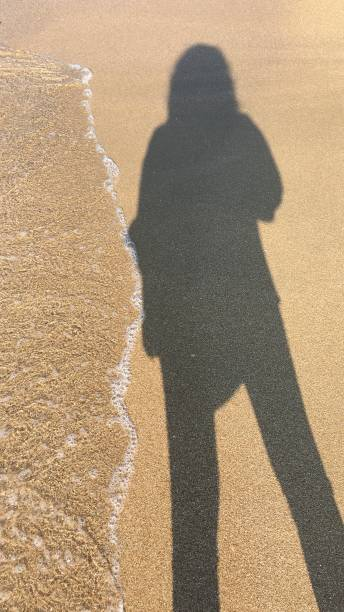 Shadow Of Person On Sandy Beach