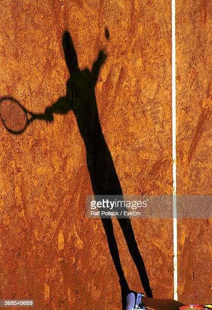 Shadow Of Person Playing Tennis On Court