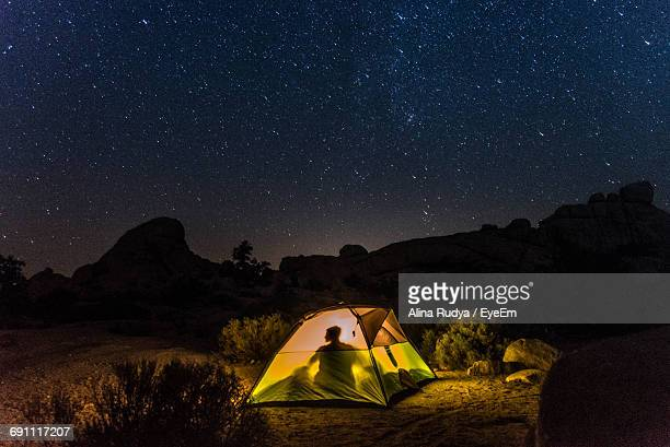 shadow of person sitting in tent by sky with stars at night - wilderness stock pictures, royalty-free photos & images