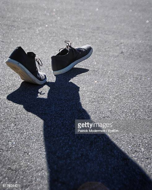 shadow of person walking on street - optical illusion stock photos and pictures