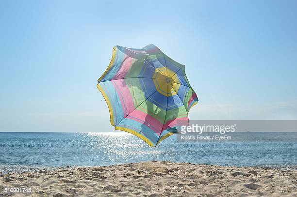 Shadow of person with umbrella jumping on beach