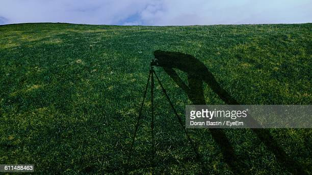 Shadow Of Photographer On Grassy Field