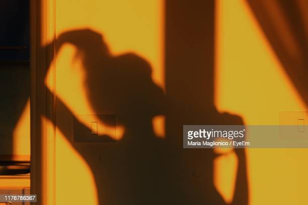 shadow of silhouette person on orange wall - 影のみ ストックフォトと画像