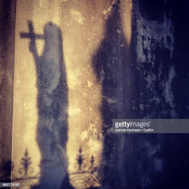 Shadow Of Statue With Cross On Wall At Cemetery