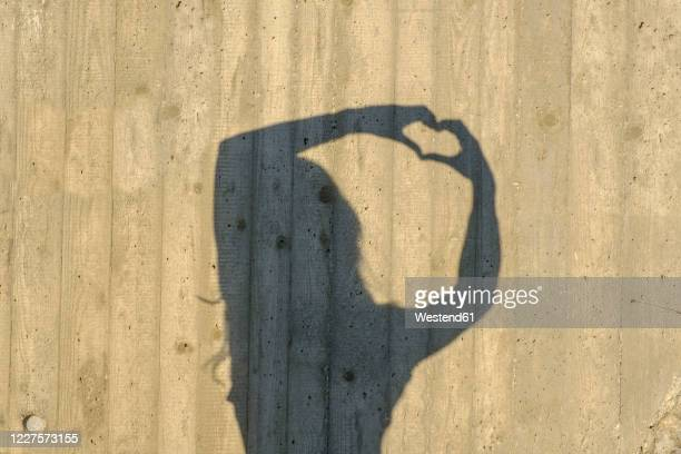 shadow of teenage girl forming heart with hands - high contrast stock pictures, royalty-free photos & images