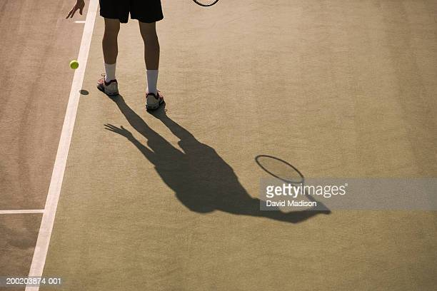 Shadow of tennis player preparing to serve ball, low section