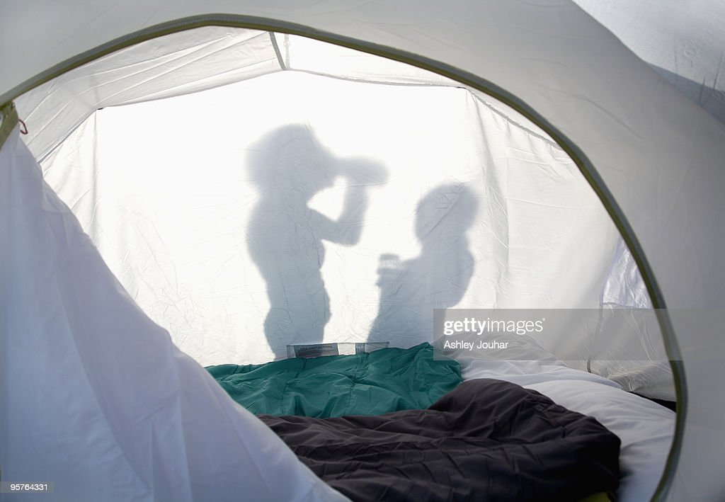 Shadow of two people outside a tent in the sunshin : Stock Photo