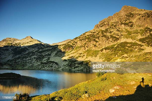 shadow of woman at sunrise in mountains by lake - pirin national park stock pictures, royalty-free photos & images