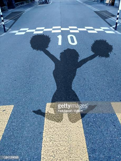 shadow of woman on road - pom pom stock pictures, royalty-free photos & images