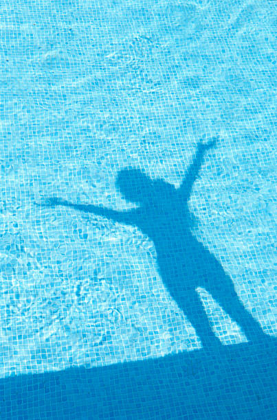 Shadow of woman standing, in swimming pool