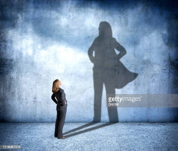 shadow of woman wearing a hero's cape - cape stock pictures, royalty-free photos & images