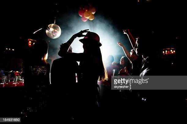 Ombre de jeunes gens danser en boîte de nuit.