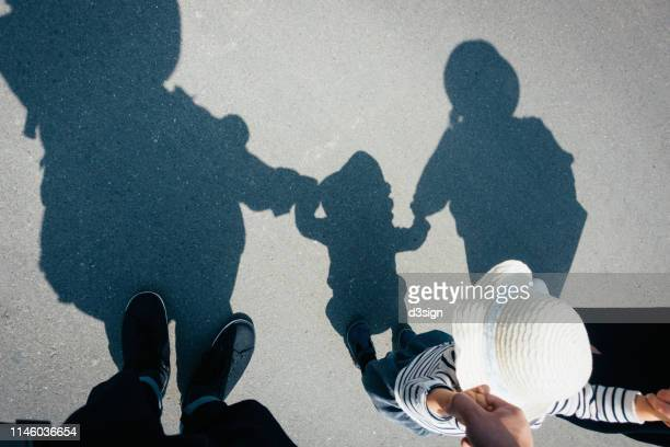 shadow on gravel path of a loving family of three holding hands walking outdoors on a lovely sunny day - sober leven stockfoto's en -beelden