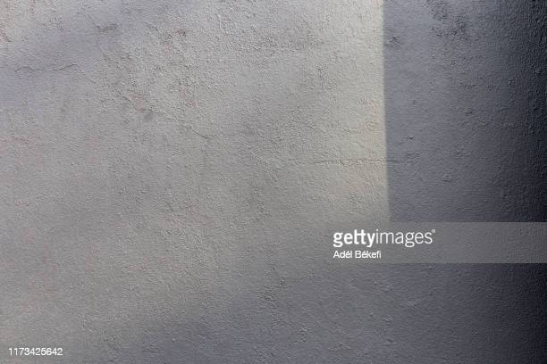 shadow on gray plastered concrete wall - textured stock pictures, royalty-free photos & images