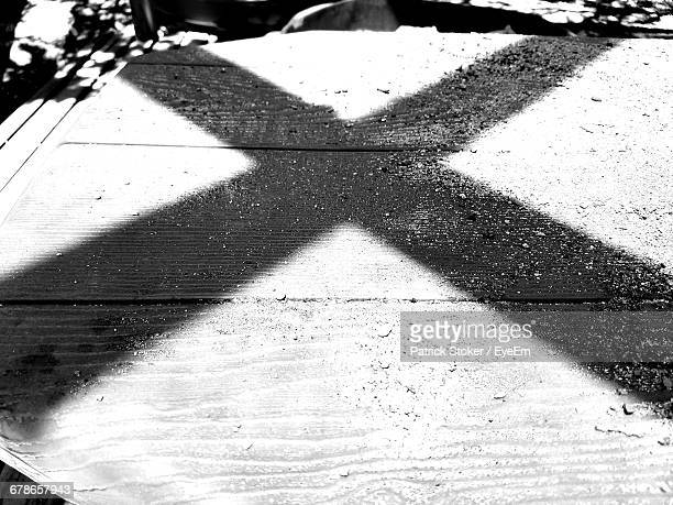 shadow on letter x on boardwalk during sunny day - letter x stock pictures, royalty-free photos & images