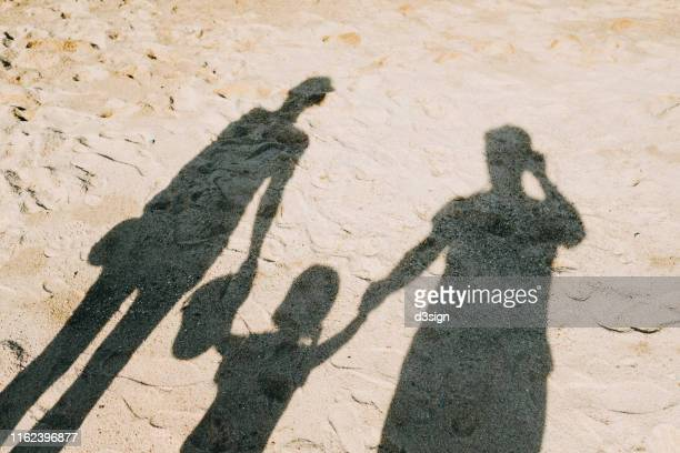 shadow on sandy beach of a loving family of three holding hands relaxing on a lovely sunny day - family with one child stock pictures, royalty-free photos & images