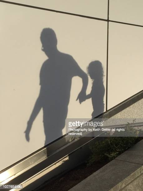 shadow people: a man and a girl together on an outdoor staircase - ombra in primo piano foto e immagini stock