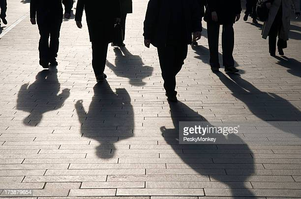 Shadow Team of Commuters Walking on Smooth Stone Walkway