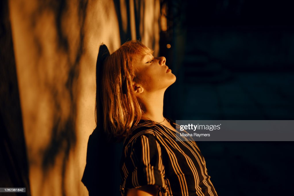 Shadowed portrait of young woman in golden hour : Stock Photo