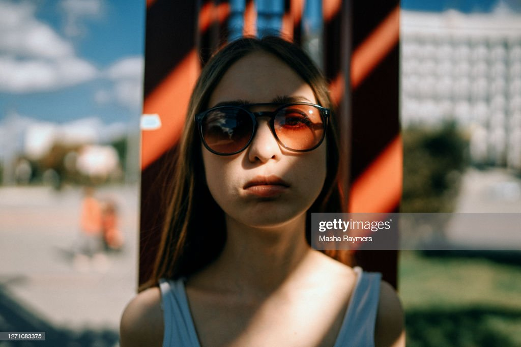 Shadowed portrait of young woman standing outside in sunglasses : ストックフォト