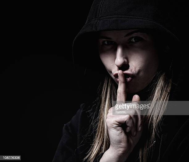 Shadowed woman asking for silence