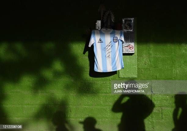Shadows are cast on a wall where a replica of Argentina's football team jersey used during the final of the FIFA World Cup Mexico '86, handwritten...