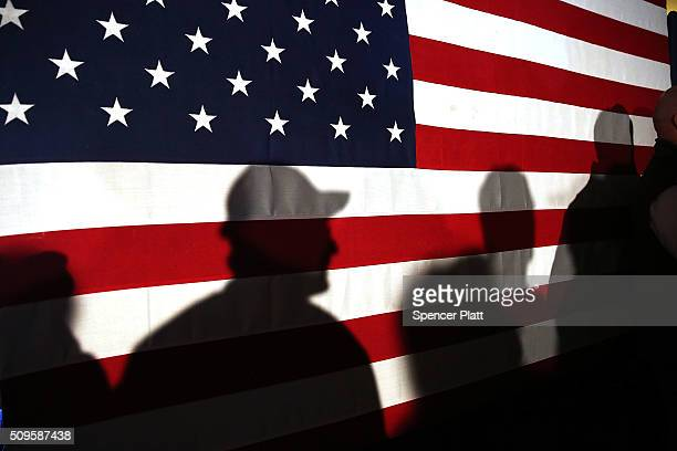 Shadows are reflected on an American Flag as people line up to speak with Ohio Governor and Republican presidential candidate John Kasich at a...