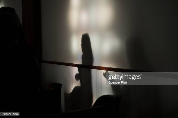 Shadows are reflected onto a wall as Knoxville residents participate in a service of prayers and hymns for peace in advance of a planned white...