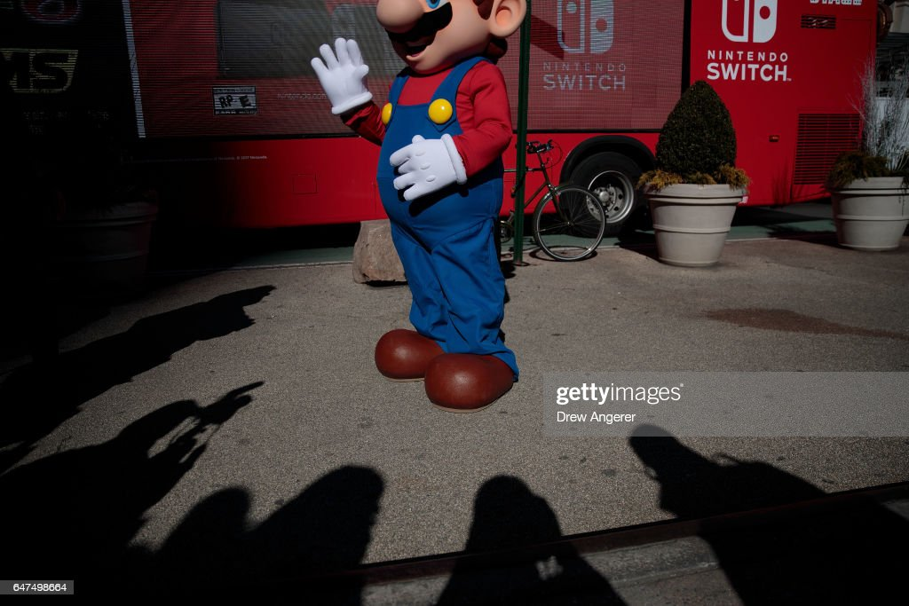 Shadows from members of the media surround a person dressed as the Nintendo character Mario at a pop-up Nintendo venue in Madison Square Park, March 3, 2017 in New York City. The Nintendo Switch console goes on sale today and retails for 300 dollars.