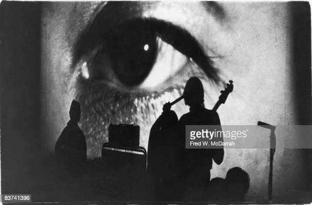Shadows of American rock band the Velvet Underground are visible in front of a closeup of a human eye projected behind them during a live performance...
