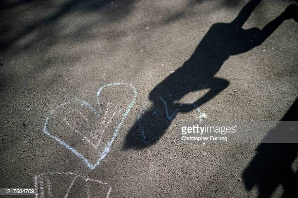 Shadows of children of key workers falls on their chalk drawings as they take part in school activities at Oldfield Brow Primary School on April 08,...