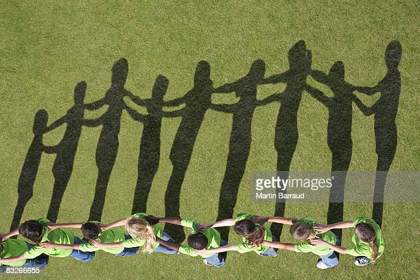 Shadows of children with hands on shoulders in a line