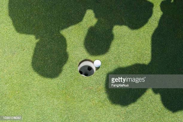 shadows of golfers over golf ball next to hole - drive ball sports stock pictures, royalty-free photos & images