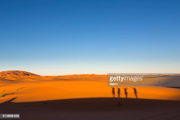 Shadows of happy people on dunes, Desert Sahara Morocco, Africa