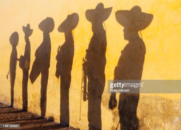 shadows of mariachi band members - mexican hat stock pictures, royalty-free photos & images