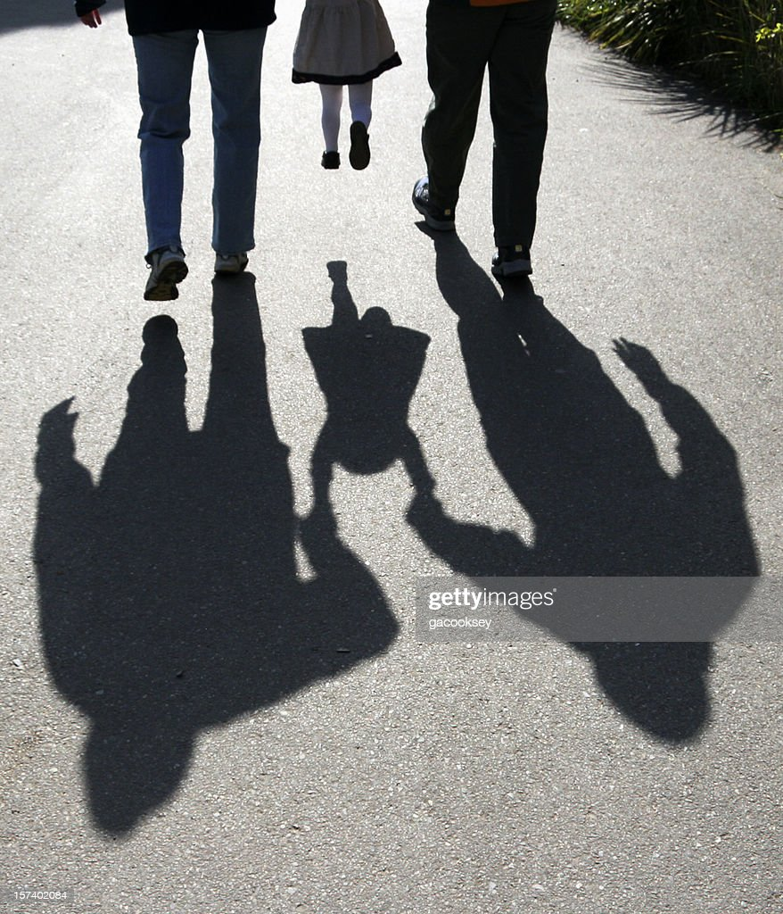 shadows of parents lifting child : Stock Photo