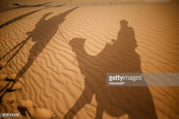 Shadows of people riding camels in the desert