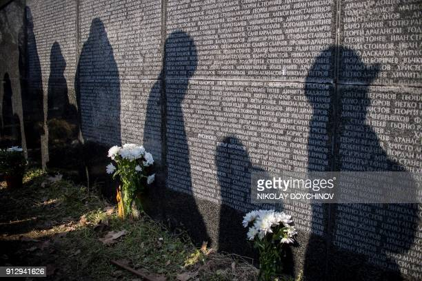 TOPSHOT Shadows of people standing in front of a monument listing victims of the Communist regime are pictured during an open air mass in central...
