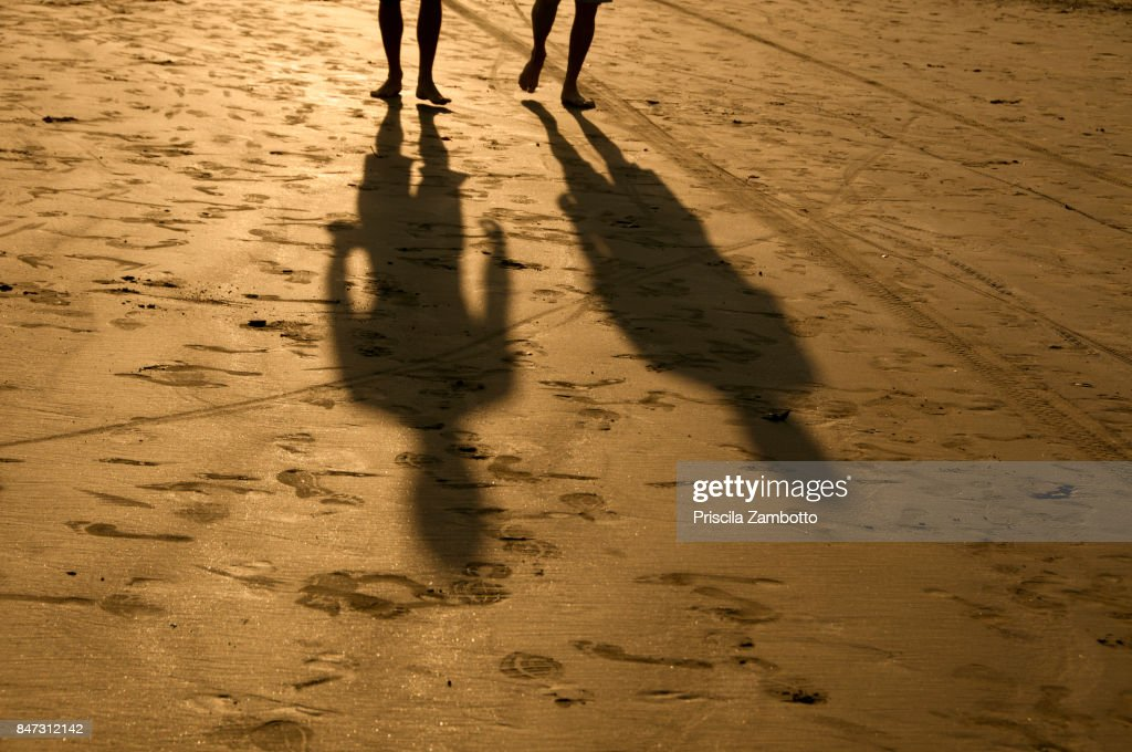 Shadows of people walking during sunset on the beach. Santos, SP, Brazil : Stock Photo